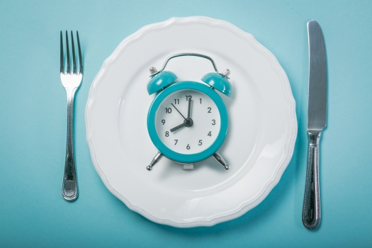 clock on blue plate symbolizing fasting